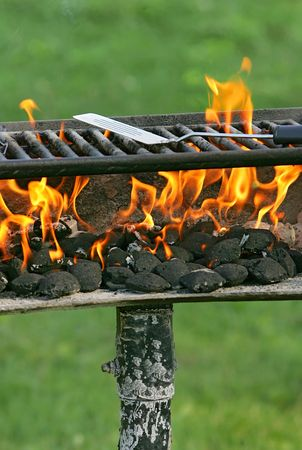 ignited: Cropped image of an old park barbecue grill in use, with a spatula waiting on top of the hot flames. Vertical format. Stock Photo