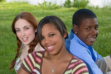 Portrait of three teenagers sitting in the grass and smiling at the camera. Horizontal format. Stock Photo - 5795254