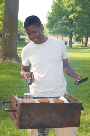 Teenage boy smiles as he cooks hamburger patties on a barbecue grill at a park. Vertical format. Stock Photo - 5795250