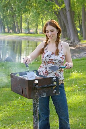 long lake: Teenage girl cooks hamburger patties on a barbecue grill at a park. Vertical format. Stock Photo