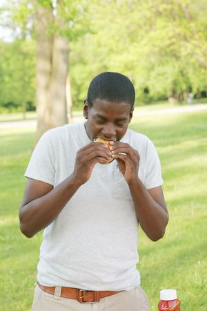 Teenage boy stands in a park while eating a hamburger. Vertical format. Stock Photo - 5795249