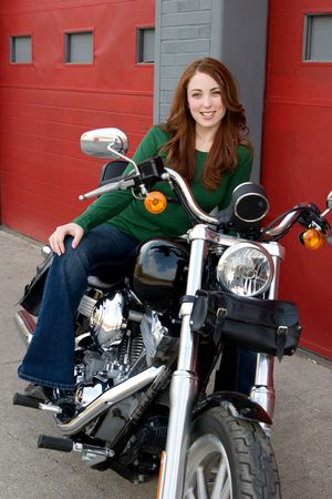 A young woman poses on a motorcycle and looks at the camera. Vertical format.