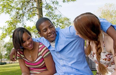 small group of 3 multi-ethnic friends playing in the park and laughing together having fun Stock Photo - 6428686