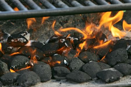 grill: burning charcoal biscuits set on fire in a barbecue grill