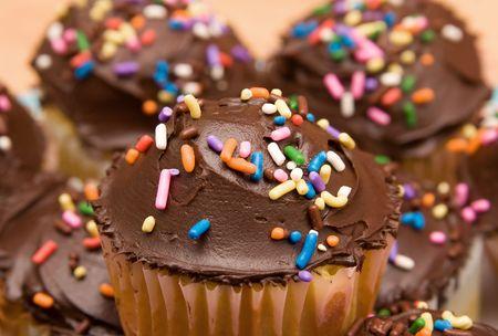 板のクローズ アップのタイトな作物にチョコレートつや消しカップケーキの大規模なグループ 写真素材