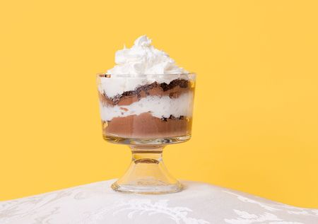 one solo low fat chocolate mousse with whipped topping sitting in a glass bowl against a yellow background