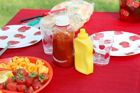 Two bottles of ketchup and mustard on an outdoor picnic table in a park setting. horizontal format photo