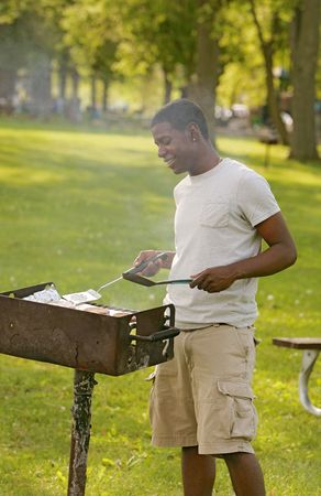 one happy twenties African American male cooking on a bbq grill outdoors in a park photo