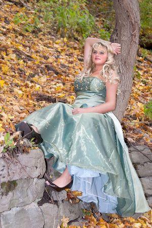 een mooie jonge blonde in een teal groen prom dress zittend op een rots in het bos