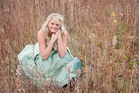 one pretty young blonde in a teal green prom dress sitting outdoors in a field photo