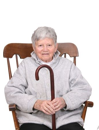 one grey haired senior adult woman sitting in a rocking chair holding a wooden cane isolated over white photo