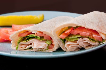 one sliced turkey wrap on a blue plate with pickles and tomatos photo