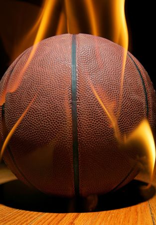 toplit basketball on hardwood floor with flames on and around it photo