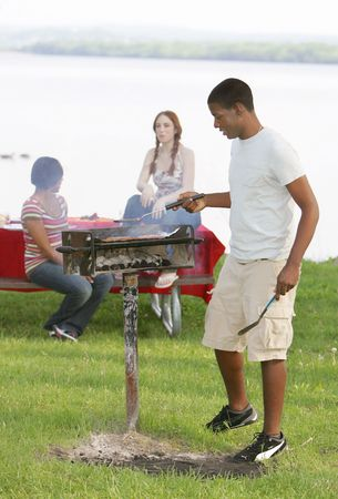 one happy twenties African American male cooking on a bbq grill outdoors in a park with two friends behind
