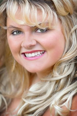 headshot portrait of a blonde young adult woman smiling. gorgeous plus size model closeup. vertical format.