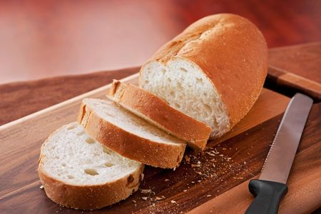 to cut: loaf of thick slice Italian bread on a cutting board. closeup horizontal format.