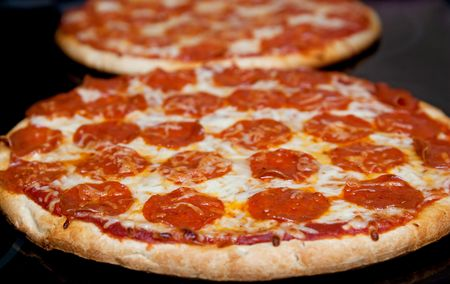 two pepperoni pizzas in a line on a black stove surface low angle Foto de archivo