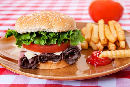 one large roast beef sandwich in sesame roll with tomatos and lettuce on plate with classic red and white checkered tablecloth