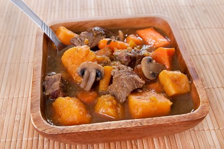 bowl of homemade beef stew with carrots and sweet potatos in a wooden bowl on placemat
