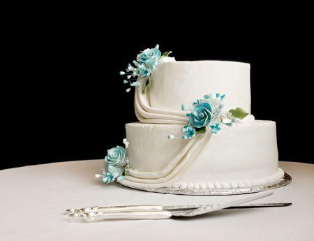 pastel de bodas: pastel de boda de blanco con flores de color azul sobre una mesa con un fondo negro
