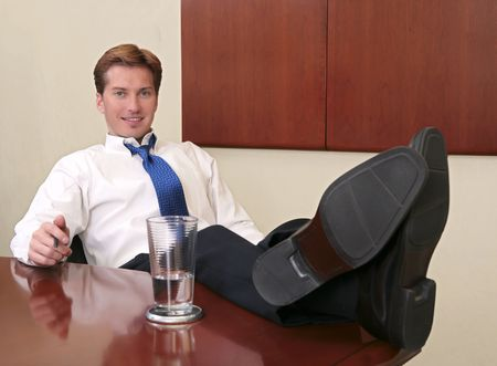 tired businessman: one thirties businessman sitting near a conference room table with his feet up Stock Photo