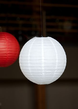 hanging red and white Japanese lantern with dark background Imagens