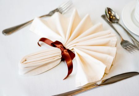white napkin and place setting with brown ribbon and flatware on a white tablecloth Stock Photo - 6552381