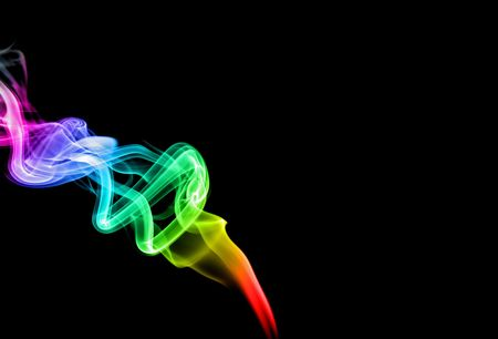 a trail of multi colored smoke over a black background