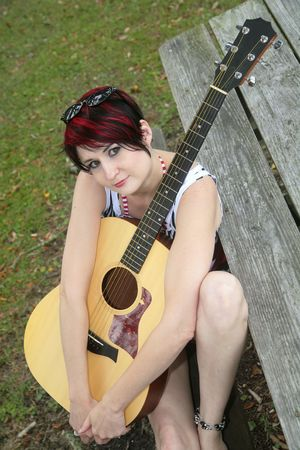 one redhead woman holding a guitar outdoors on a picnic table bench Stock Photo