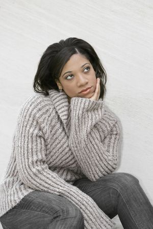 young attractive African American woman thinking outdoors against a light colored wall