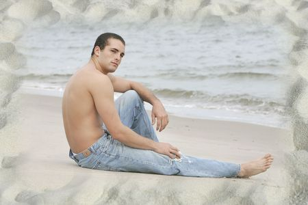 one young fit twenties guy sitting topless on a beautiful sandy beach photo