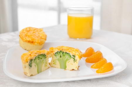 scrumptious: breakfast plate of broccoli frittata muffins and orange slices on a white plate with juice. high key, horizontal format. Stock Photo