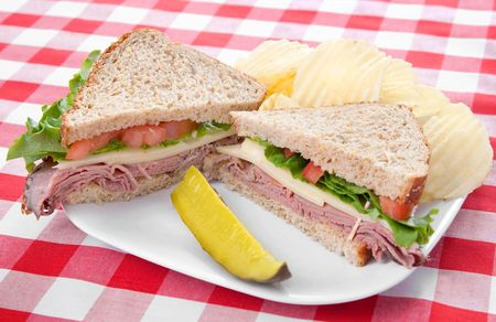 one sliced large roast beef sandwich with a pickle and chips on a white plate with classic red checkered tablecloth