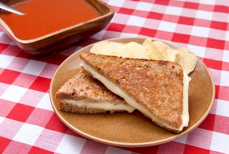 grilled potato: basic grilled cheese sandwich on toasted bread with chips and a big bowl of tomato soup on a traditional checkered red and white tablecloth Stock Photo