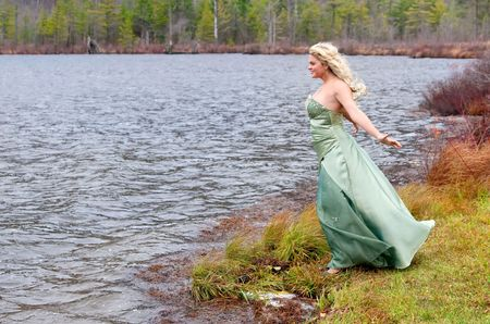 beautiful location: young teen blonde girl in a teal prom dress near the lake Stock Photo