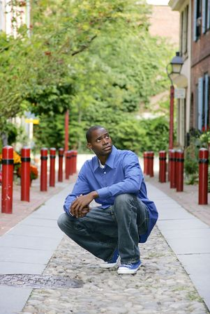 one young African American man squatted down on the cobblestone road looking up at the historic buildings