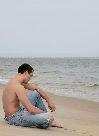 one pensive sad looking young fit man sitting on a beach near the ocean photo