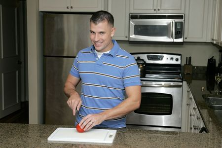 one attractive 20s man working on cutting a tomato in a modern kitchen with stainless appliances photo