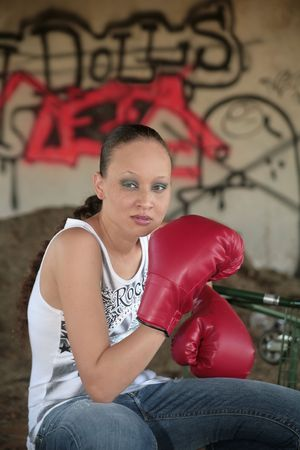 one young minority woman sitting outdoors near graffiti with boxing gloves on looking tough photo