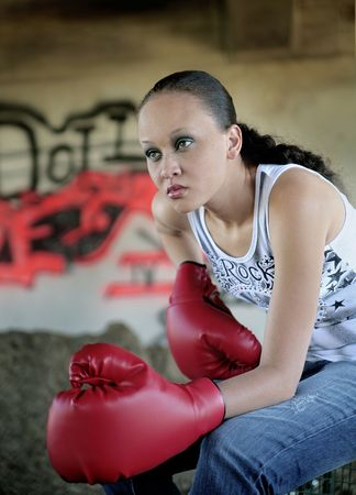 one young minority beautiful woman sitting outdoors in front of graffiti with boxing gloves on looking serious and ready to fight photo