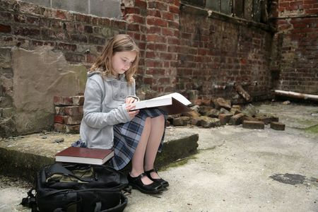 one young cute female student out of place in an old, run down brick warehouse district studying while alone photo