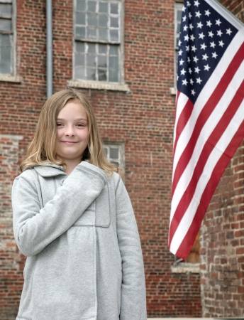 allegiance: one young cute child with hand on her heart near an American Flag outdoors