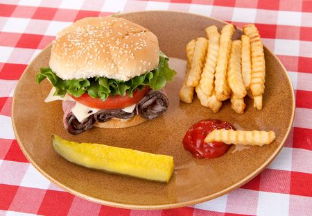 one large roast beef sandwich in sesame roll with tomatos and lettuce on plate with classic red and white checkered tablecloth photo