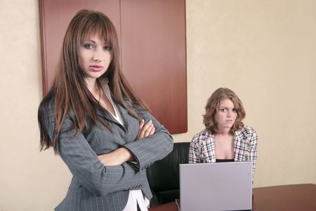 two attractive business women in an office or conference room  photo