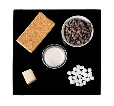 graham: ingredients for smores truffle candy on a black plate including graham crackers, chocolate chips and mini marshmallows