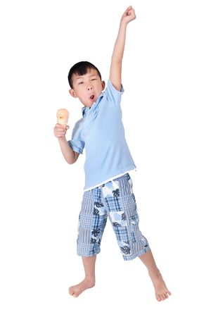one happy asian young boy celebrating and eating ice cream isolated on white photo
