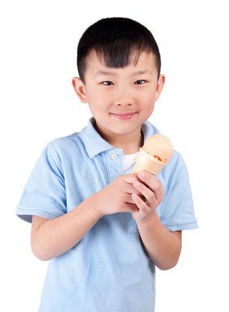 one happy asian boy eating orange sherbet isolated on white Stock Photo