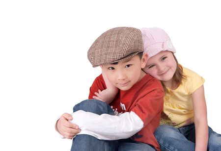 one happy young Asian boy and caucasian girl sitting together over white Stock Photo - 6726716