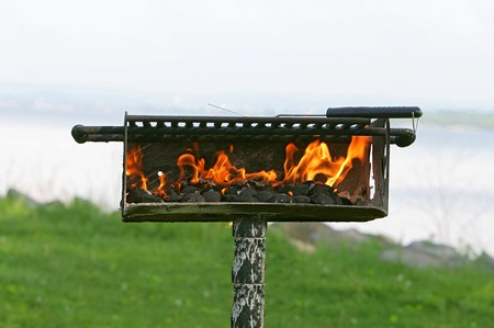 charcoal on fire heating up a barbecue pit before cooking Stock Photo