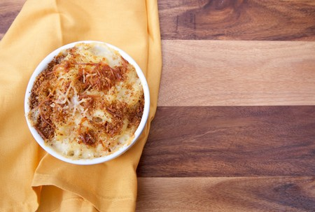 homemade macaroni and cheese in a ramekin with copyspace on a yellow napkin and wood surface photo